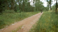 The countryside. bike rides along the dirt path among the trees and bushes video