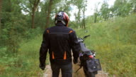 The countryside. Motorcyclist goes into full gear to his motorcycle video