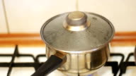 The Cover Moves away from the Pressure of Steam in the Pan of Food on the Stove Home Kitchen. Slow Motion video