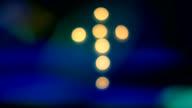The cross of candles, luminous cross, light reflection. video