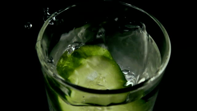 The cucumber slice falls into the water. Slow motion video