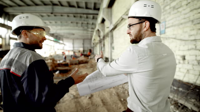 The customer in a protective helmet verifies the work of builders on the object under construction, people walk through the building of the former factory video