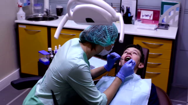 The dentist examines the teeth teenager video