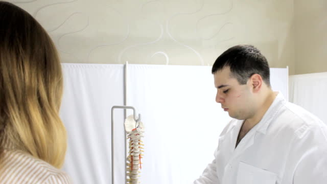 The doctor advises patient on subject of spine video