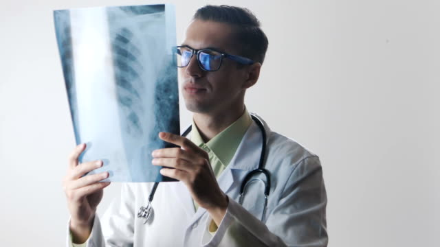 The doctor is studying an X-ray. The medical worker makes a good diagnosis video