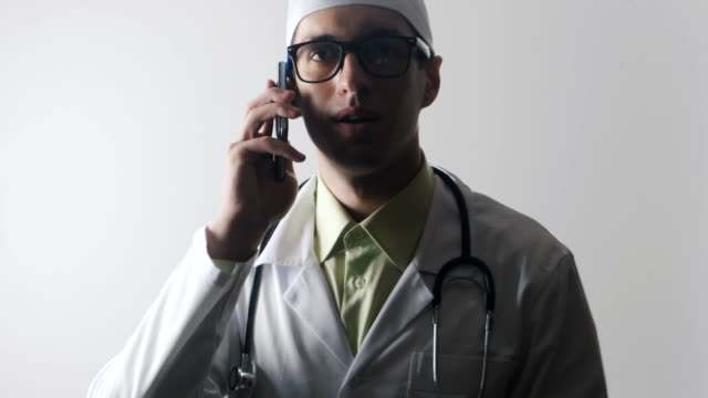The doctor speaks on a mobile phone. A medical worker makes a phone consultation. video