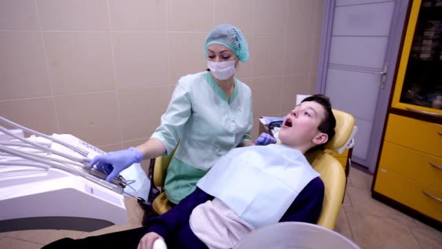 The doctor treats a boy teeth dental drill video