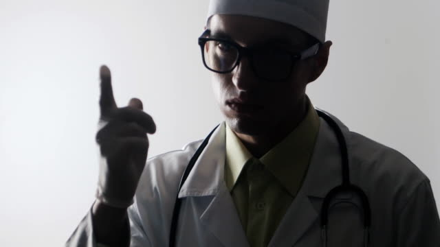 The doctor waves his index finger menacingly. Strict medical worker video