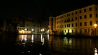 The dynamic view on night venice architecture from moviing gondola boat slowmotion video