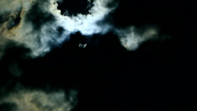 The eclipse of the sun in the sky. The eclipse through the cloud video
