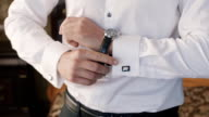 The elegant man in a white shirt wears wristwatches on hand video