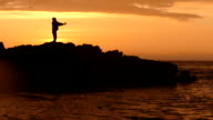 The evening silhouette of a fisherman on a fishing trip video