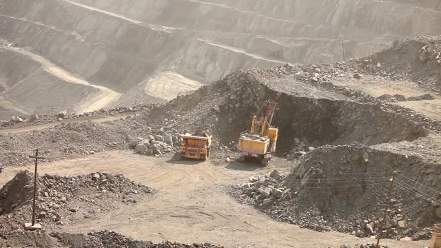 The excavator and dumper in the quarry, Large yellow excavator loaded ore into a dumper video