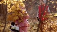 The family looks in the camera through yellow leaves video