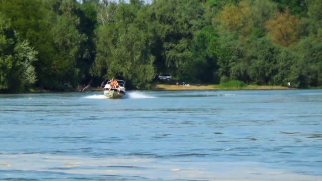 The family rides the yacht over the side. Three people are sitting in the bow of the motor boat. The Kuban River video