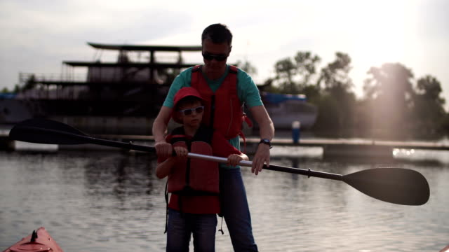 The father teaches the son how to use an oar in a kayak video