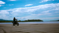 The feeling of freedom and Moto aesthetics. Motorcyclist riding on his bike on sandy beach video