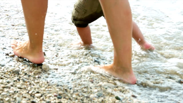 The feet of a young woman and a young child in the band of the sea video