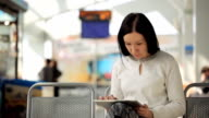 The female is working with tablet pc waiting in airport hall video