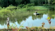 The fisherman floats on the river in an inflatable boat. Moving camera by slider. Activities in the wild video