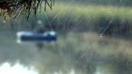 The fisherman floats on the river in an inflatable boat. Spider wove a web of the foreground. Activities in the wild video