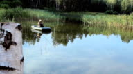 The fisherman floats on the river in an inflatable boat. The camera looks out of birch. Activities in the wild video