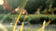 The fisherman floats on the river in an inflatable boat. The rays of the sun play in the frame. Activities in the wild video