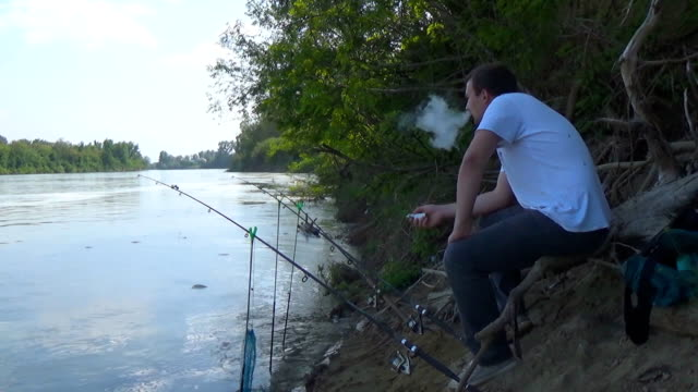The fisherman sits near the fishing pole on the river bank and smokes an electronic cigarette video