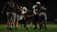 The football is snapped and run down the field during a game at night video