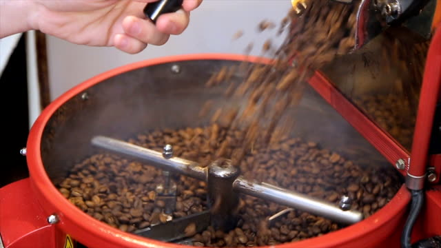 The freshly roasted coffee beans from a coffee roaster being poured into the cooling cylinder. video