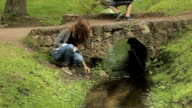 The girl at the small bridge throws leaves into the stream, Peterhof, Saint Petersburg video