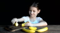 The girl cut the banana on a cutting Board video