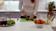 The girl cut the plums with a knife on the Board video