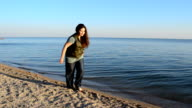 The girl does a twine on a beach video