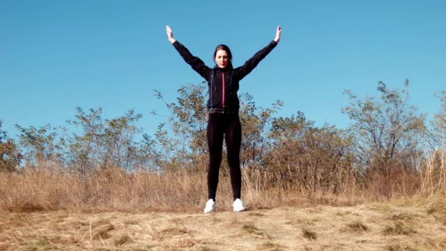 The girl does exercises in autumn park video
