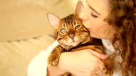 The girl embraces and kisses a Bengal cat. Close-up. video