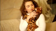 The girl embraces and kisses a Bengal cat. video