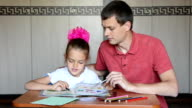 The girl first grader and Dad decide logical problems in the textbook video