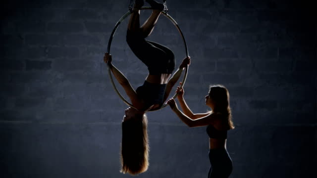 The girl helps her partner to do the trick on the aerial hoop video