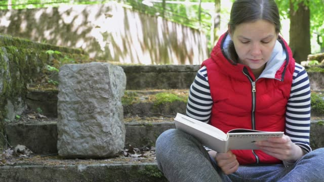 The girl in a red jacket and a striped sweater, reading a big book in a beautiful location on the ancient steps. Slow motion. video