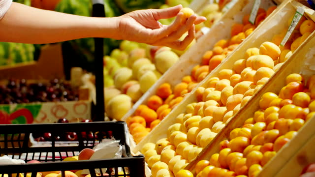 The girl in a supermarket selects the fruit. video