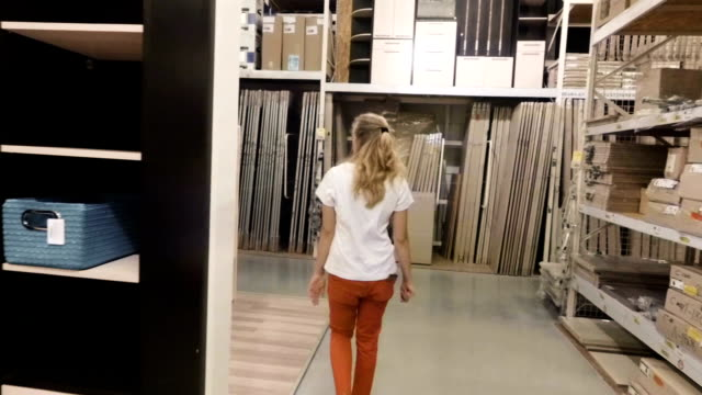 The girl in the store chooses furniture for the house. Slow motion video