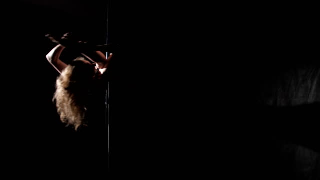 The girl is dancing on the pole, backlight video