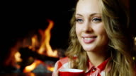 The girl is drinking tea near the fireplace video