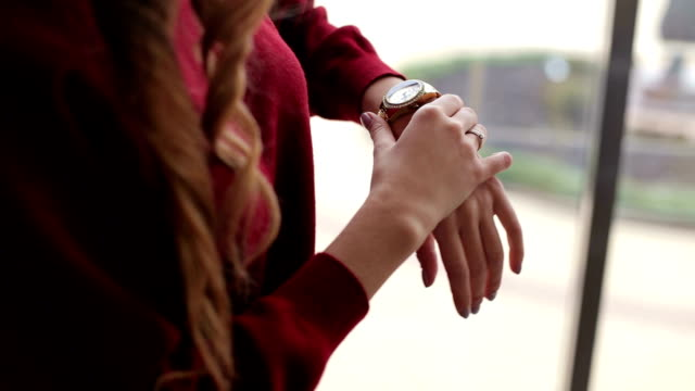 The girl looks at her watch. Close-up. The girl waits for the boyfriend. video