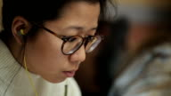 The girl of the Asian appearance in glasses and headphones in ears reads video