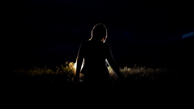 The girl stands near the car in the headlight at night. Happy video