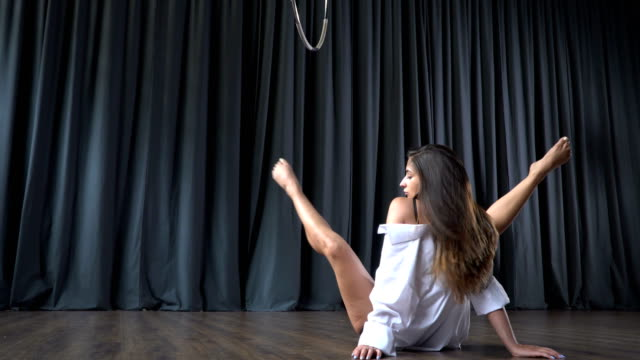 The girl stretches before the making tricks on the aerial hoop video