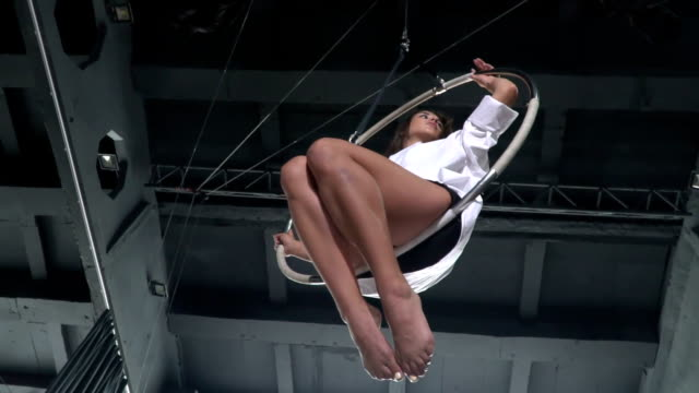 The girl sways in the aerial hoop in slowmotion video