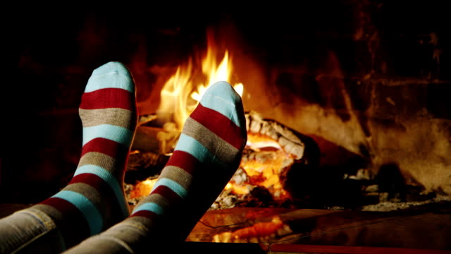 The girl warms his feet by the fireplace video